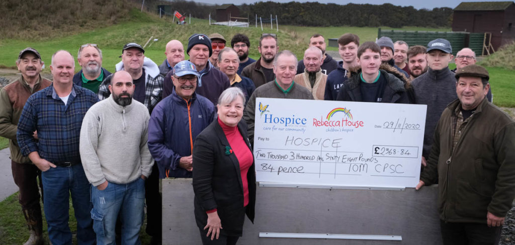 Photo of a group of competitors standing behind chairman Peter Kelly as he presents a cheque to Hospice CEO Anne Mills